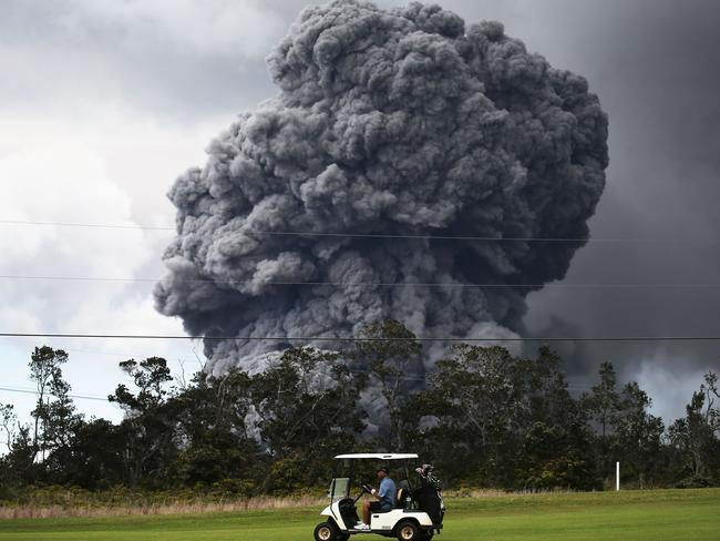 The game must go on: a man drives a cart at a golf course as an ash rises in the distance. Picture: AFP
