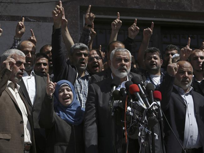 Supporters chant Islamic slogans as Hamas Supreme Leader Ismail Haniyeh, centre, announces the arrest of a suspect in the March shooting death of Mazen Faqha, as Faqha's widow Nahed Asida, stands next to him. Picture: AP
