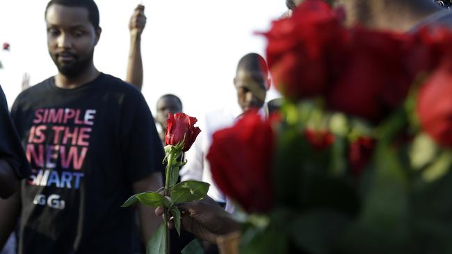 Peaceful demonstration ... roses are handed out to Ferguson protesters. Picture: AP Photo/Jeff Roberson)