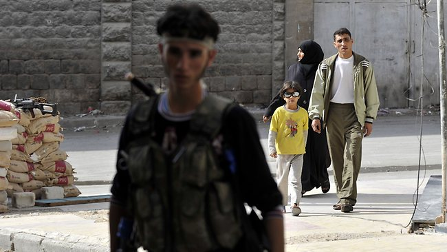 Members of a Syrian family walk past a rebel in the northern city of Aleppo on October 8, 2012. A string of rebel bastions across Syria was rocked by regime shelling and clashes, as several army checkpoints also came under attack, with more than 60 people killed nationwide, a rights group said. AFP PHOTO/Tauseef MUSTAFA