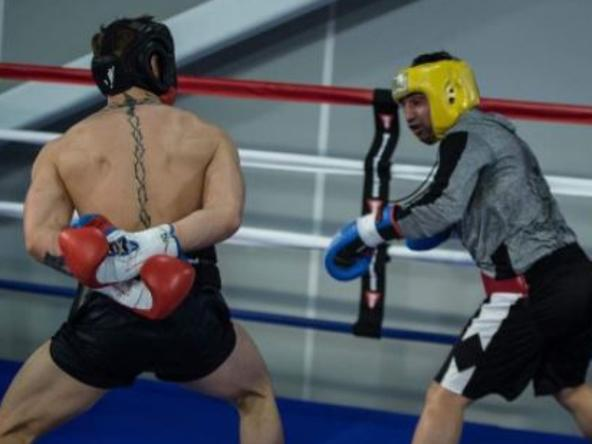 Conor McGregor stands with his hands behind his back in sparring with retired boxer Paulie Malignaggi.
