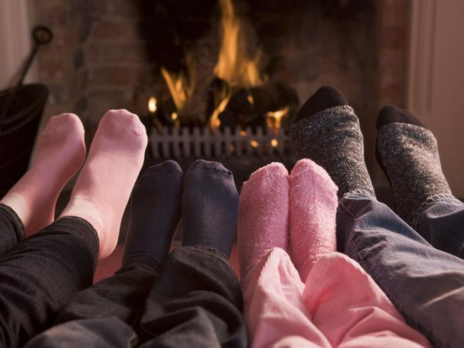 "The ""never-leaver"" ... A family warm their feet near a fireplace."