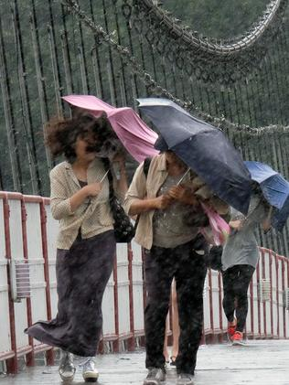 Battling winds ... residents try to walk in strong wind on a suspension bridge. Picture: Sam Yeh