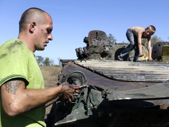 Salvage ... Alexander Bespalko, left, with his son Denis loosen parts from a burnt-out Ukrainian armoured personnel carrier in the village of Hrabske, eastern Ukraine, at the weekend. Source: AP