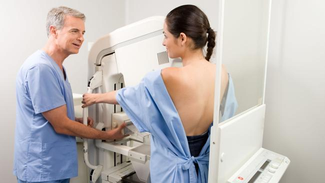 Technician performing a mammography mammogram screening test at clinic.