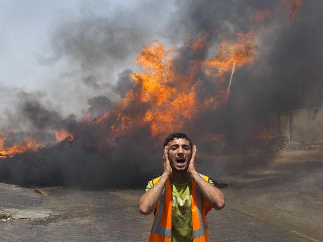Under siege ... Palestinian firefighters try to extinguish a fire at a UN storehouse after an Israeli military strike in an area west of Gaza City on July 12, 2014. Picture: Mahmud Hams