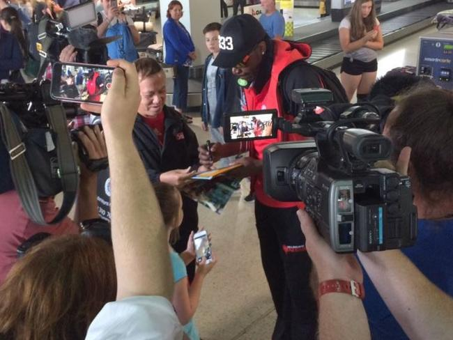 Gayle signs autographs as he arrives back in Melbourne