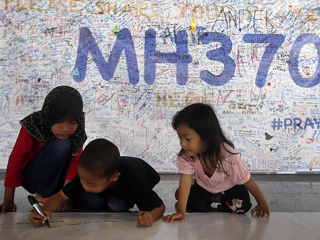 Young children write messages to express their support for the missing passengers.