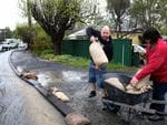 Mark Baryczka helps his neighbour Rebecca Francis sand bag her driveway, on Onkaparinga Valley Rd. Picture: Dean Martin