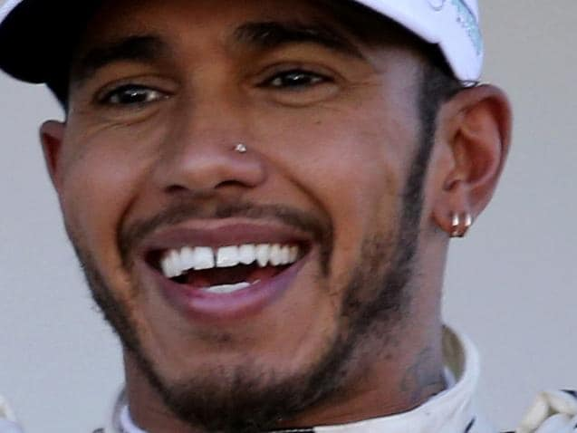Mercedes driver Lewis Hamilton of Britain poses on the podium for his team crew after winning the Japanese Formula One Grand Prix at Suzuka Circuit in Suzuka, central Japan, Sunday, Oct. 8, 2017. (AP Photo/Toru Takahashi)