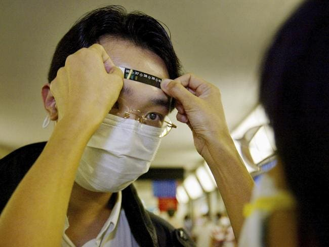 Nurses and doctors check the temperatures of travellers amid a SARS outbreak.