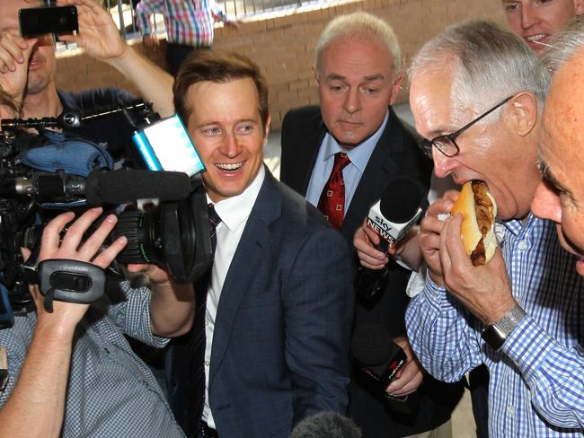 Prime Minister Malcolm Turnbull gets stuck into a democracy sausage during campaigning at Gladesville Public School. Picture: AAP