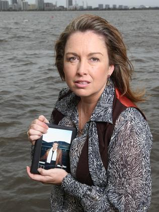 Tracy Johnston holding a photo of her partner Mark Hutton who was murdered in 2010.