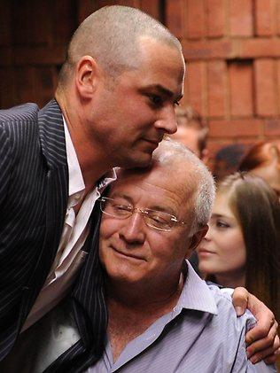 Carl Pistorius and father Henke hug on February 21, 2013 at the Magistrate Court in Pretoria where Oscar Pistorius is facing a bail hearing after being cgharged with murder. AFP / Joe Alexander