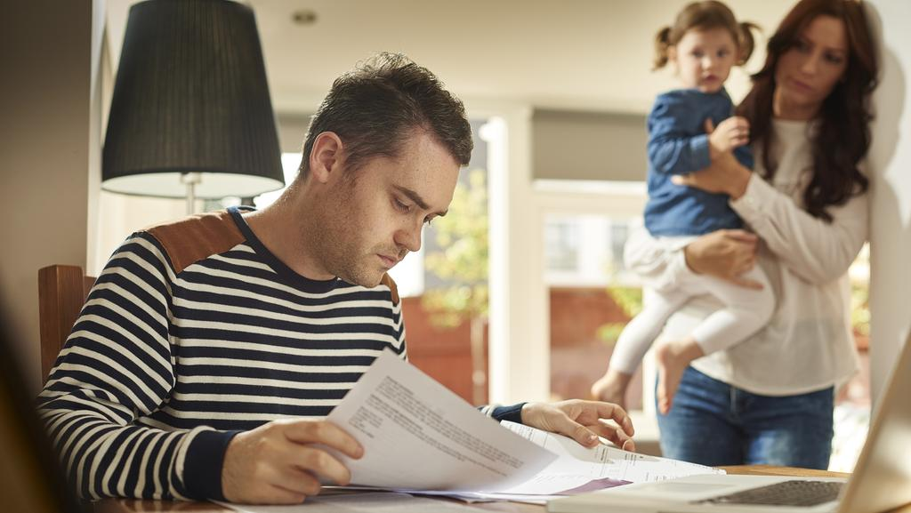A young husband and father sits at a dining table looking through the household bills. Picture: Supplied