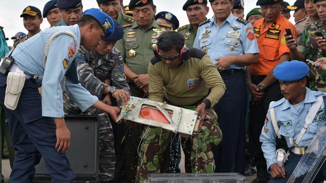 Retrieved ... Indonesian officers move the Flight Data Recorder of the AirAsia flight QZ8501 into a suitable protective transportation case. Picture: Adek Berry