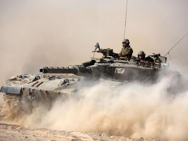 Won't back down ... An Israeli Merkava tank rolls near Israel's border with the Gaza strip.