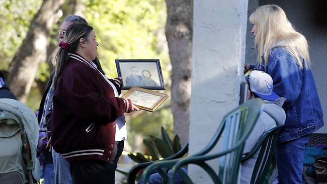 Wanda Carter shows friends some of the photos that were saved from the home of Jeff Bush, 37, who was swallowed by a sinkhole that opened up underneath his bedroom as he slept. (AP Photo/Scott Iskowitz)