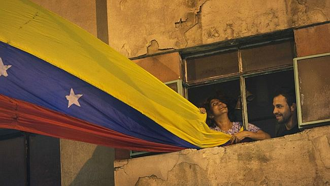 Flag waving... A woman flies Venezuela's national flag from a Caracas apartment block. Pi