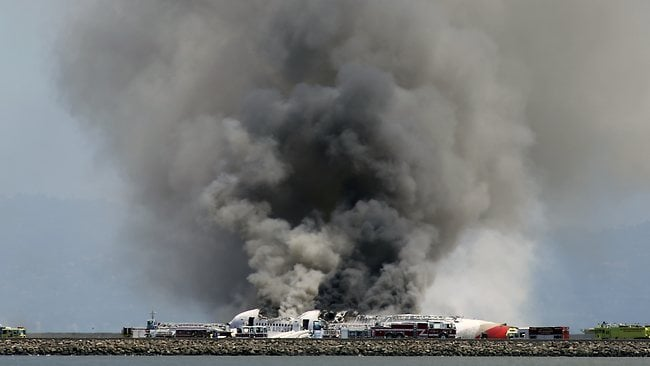 Smokes rises from Asiana Flight 214 after it crashed at San Francisco International Airport in San Francisco. (AP Photo/Bay Area News Group, John Green)