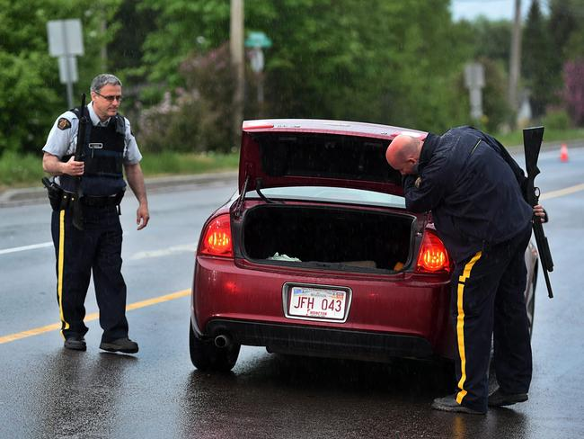 No where to hide ... police officers check a car at a roadblock in Moncton.