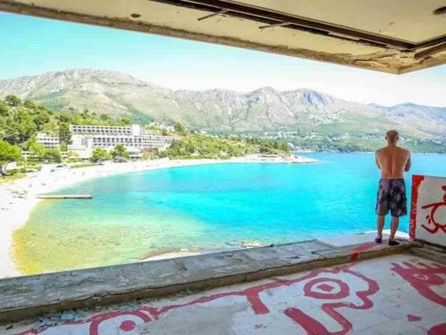 Kupari, Croatia - July 18, 2017 : A man standing in an abandoned old building of hotel Pelegrin with the view of the sea beach in Kupari, Croatia.