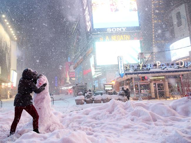 Having fun ... a woman decorates a snowman in Times Square. Picture: Yana Paskova/Getty Images/AFP