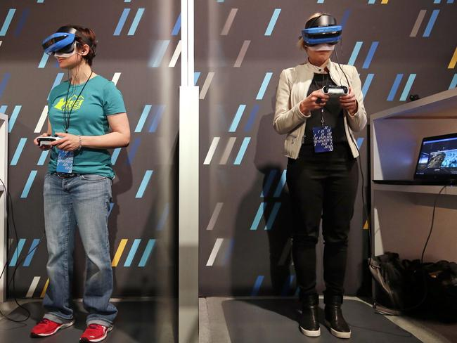 Two women wearing HoloLens devices try out a Windows mixed reality immersive experience. Picture: Elaine Thompson