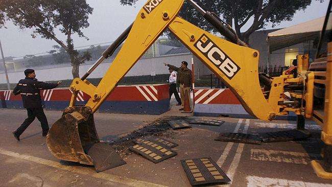 Heavy measures ... Indian police remove barricades that had been erected as a safety measure outside the main entrance of US ...