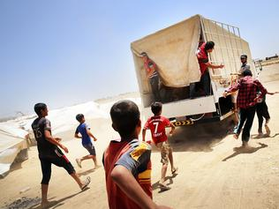 Resist or perish? Desperate Christian Iraqi's at the Khazair displacement camp chase a Red Crescent society truck delivering food and other items.