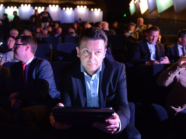 Nick Xenophon checks results on a tablet at the post-election party at the Palace Nova Cinema in Adelaide. Picture: AAP Image/Brenton Edward