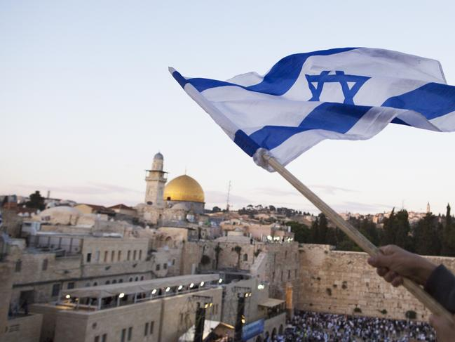 Israelis wave their national flags during a march next to the Western Wall. Picture: Getty