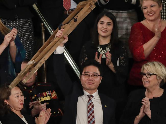 Ji Seong-ho holds up his crutches after his introduction by President Trump. Picture: J. Scott Applewhite/AP