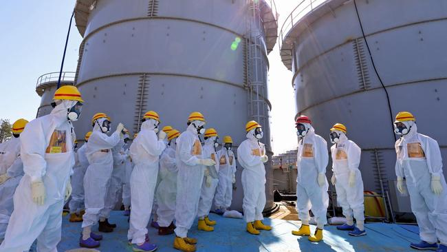 Fukushima ... Shinzo Abe, Japan's prime minister, third right wearing a red helmet, is briefed by workers at the Fukushima Dai-ichi nuclear power plant, which was crippled in the 2011 tsunami. A 6.8-magnitude quake was registered near the site on Friday.