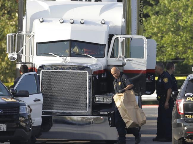 San Antonio police officers investigate the scene where eight people were found dead in a semi-trailer outside a Walmart store. Picture: Eric Gay/AP