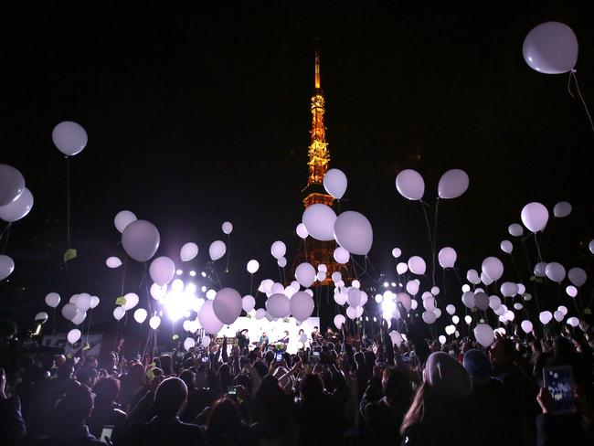 Festive ... people release balloons near Tokyo Tower to celebrate the New Year. Picture: AP Photo/Eugene Hoshiko