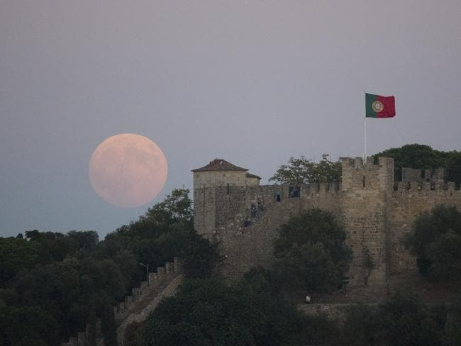 The full moon rises behind Lisbon's St. George castle. Picture: AP / Armando Franca