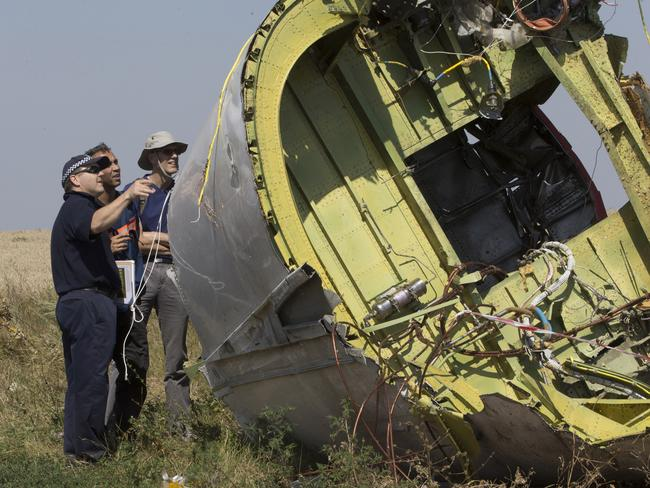 Looking for clues ... Australian and Dutch experts examine a piece of the Malaysia Airlines Flight 17 plane. Picture: AP Photo/Dmitry Lovetsky
