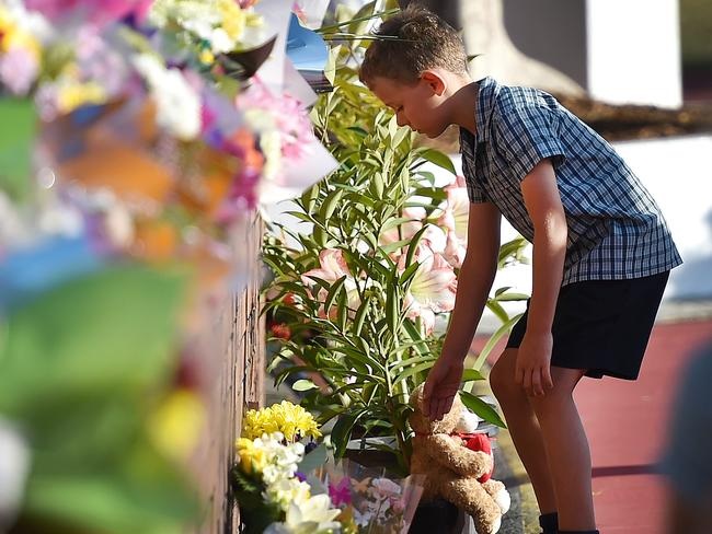 Tragedy: A immature child places flowers during Dreamworld a day after a tragedy where 4 people were killed. Picture: Nigel Hallett