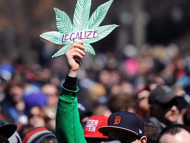 A man holds up a sign advocating the legalisation of marijuana at the 43rd annual Hash Bash on the University of Michigan.