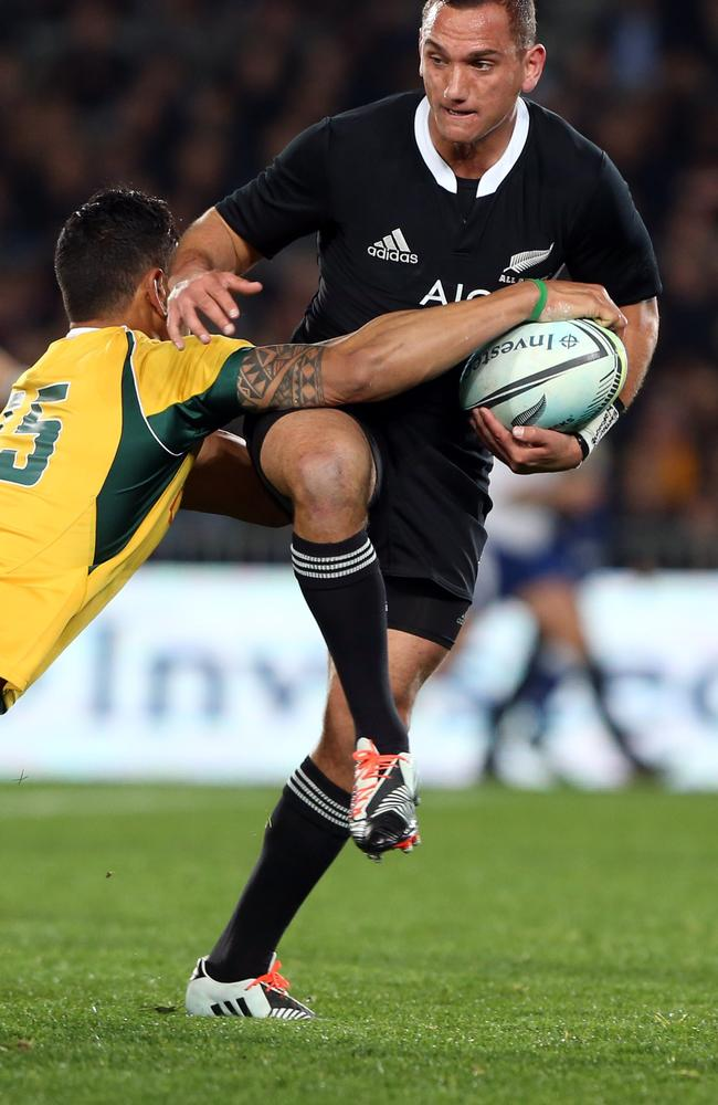 Israel Folau tackles All Blacks halfback Aaron Cruden at Eden Park.