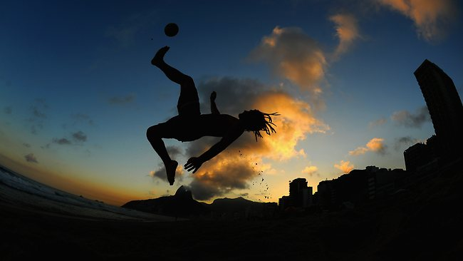 A man performs an overhead kick as he plays football on Ipanema beach ahead of the FIFA Confederations Cup in Brazil. Picture: Michael Regan