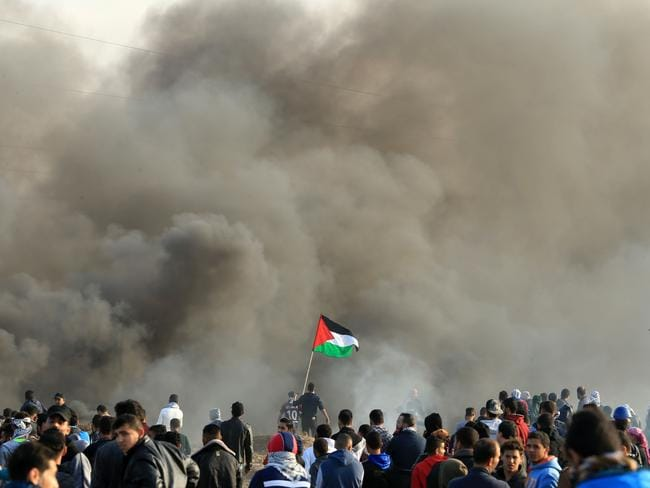 Palestinian protesters wave the national flag during clashes with Israeli security forces near the border fence with Israel, east of Gaza City. Picture: AFP
