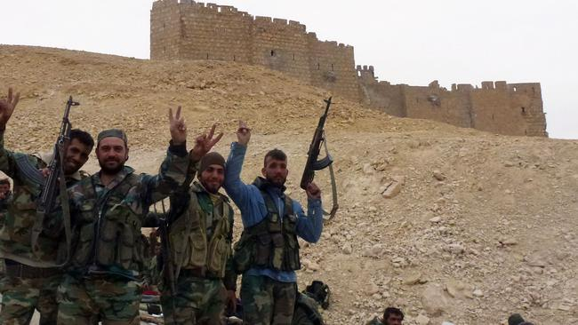 'Fatal blow' ... Syrian pro-government forces celebrate next to the Palmyra citadel during a military operation to retake the ancient city from the Islamic State (IS) group. Picture: AFP/Maher AL MOUNES