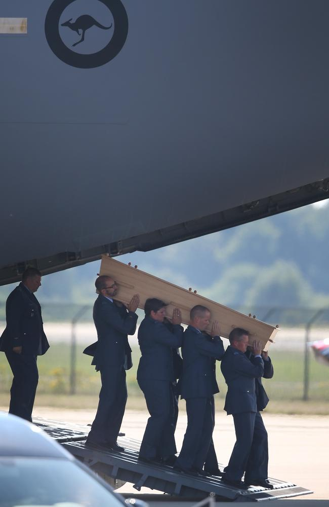 Dutch military personnel carry a coffin containing an unidentified body from the crash of MH17 from a Royal Australian Air Force C47 to a waiting hearse at Eindhoven airport, Netherlands. Picture: Peter Macdiarmid