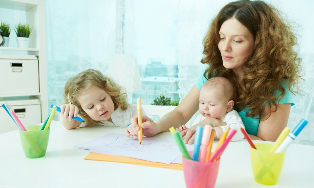 Nanny with two children drawing