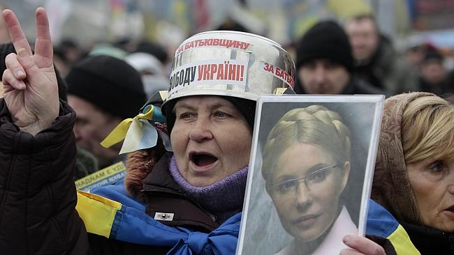 Jailed...Opposition supporters hold up a portrait of former prime minister Yulia Tymoshenko.
