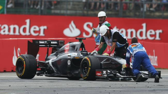 Marshals struggle to clear Sutil's Sauber from the circuit.