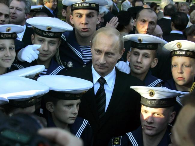 Vladimir Putin meets with students of a naval boarding school while attending the unveiling of a monument to late Anatoly Sobchak, St. Petersburg's liberal Mayor, in St. Petersburg, Russia, 2006.