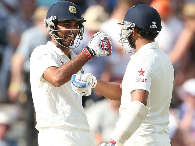 India's Mohammed Shami (L) and India's Bhuvneshwar Kumar celebrate after scoring a half century.
